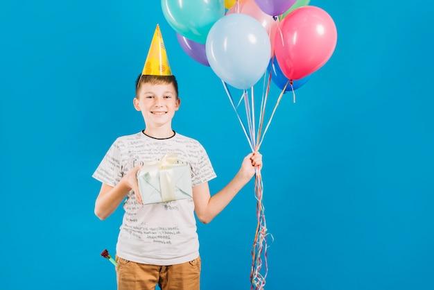 Portrait d'un garçon heureux tenant des ballons colorés et un cadeau d'anniversaire sur fond bleu