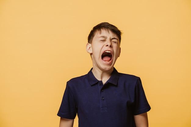 Portrait d'un garçon hurlant à haute voix, les yeux fermés, porte un t-shirt violet foncé, isolé sur un mur jaune avec un espace libre pour votre annonce. concept d'émotion de personnes.