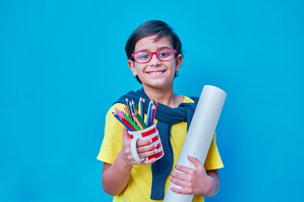 Un portrait d'un garçon intelligent et studieux avec des lunettes rouges dans un tshirt jaune tenant à la main une tasse avec beaucoup de crayons de couleur et un rouleau de papier à peindre sur le mur bleu copy space