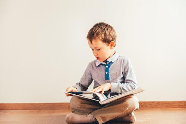 Portrait de garçon intéressé à lire un livre.