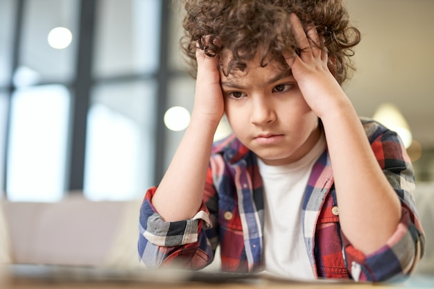 Portrait d'un garçon latin fatigué tenant sa tête, l'air triste assis au bureau et étudiant à la maison. éducation en ligne, concept d'enseignement à domicile