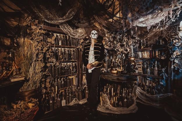 Portrait d'un garçon maquillé d'un maniaque fou debout dans un intérieur fabuleux et regardant la caméra