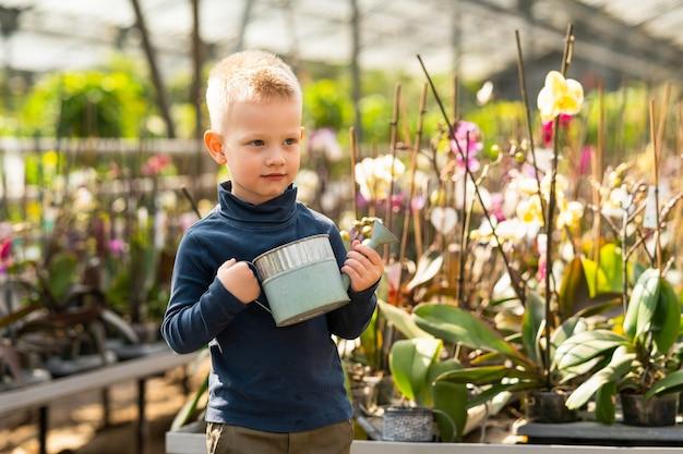 Portrait d'un garçon mignon avec un arrosoir dans ses mains à effet de serre