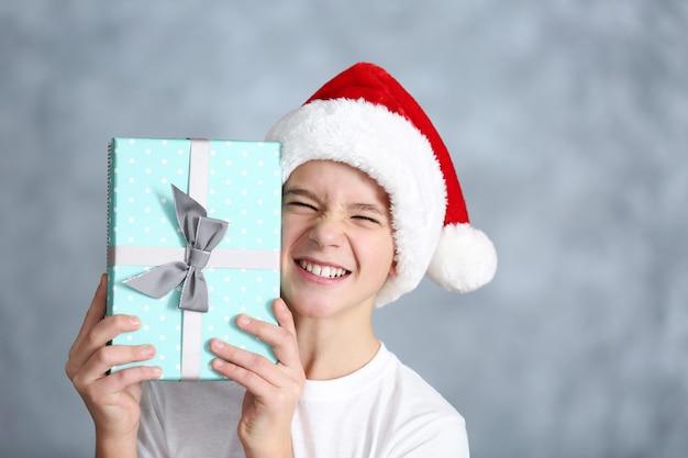 Portrait d'un garçon mignon avec une boîte-cadeau bleue se bouchent