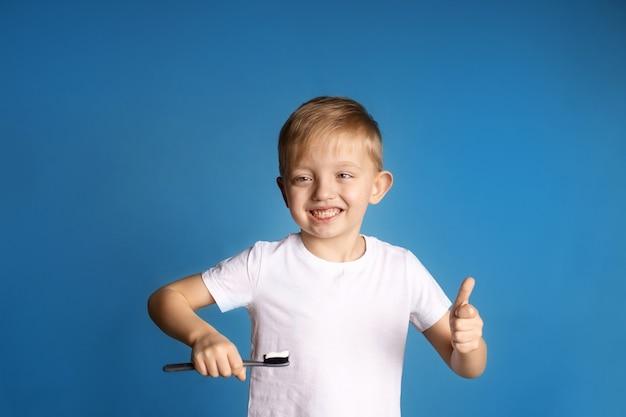 Portrait d'un garçon mignon heureux 5-6 ans sur un mur bleu, l'enfant se brosse les dents, mode de vie sain