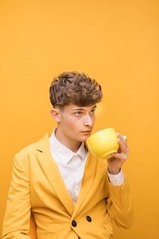 Portrait d'un garçon à la mode, buvant dans une tasse