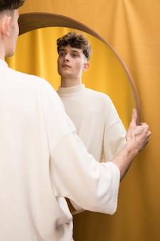 Portrait d'un garçon à la mode devant un miroir