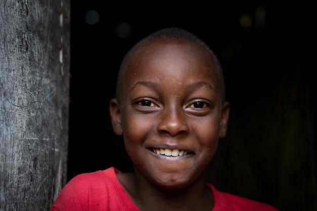 Portrait de garçon noir africain debout près de sa pauvre maison seul
