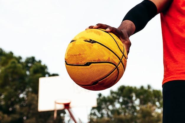 Portrait d'un garçon noir afro-américain tenant le ballon de basket sur un terrain de basket urbain.