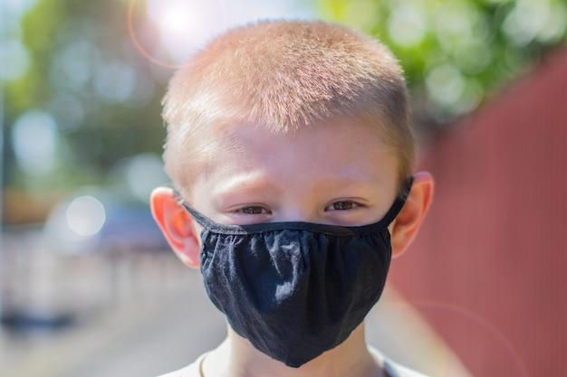 Portrait d'un garçon portant correctement son masque facial de protection en plein air