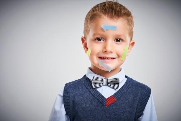 Portrait d'un garçon posant sur blanc avec des flèches