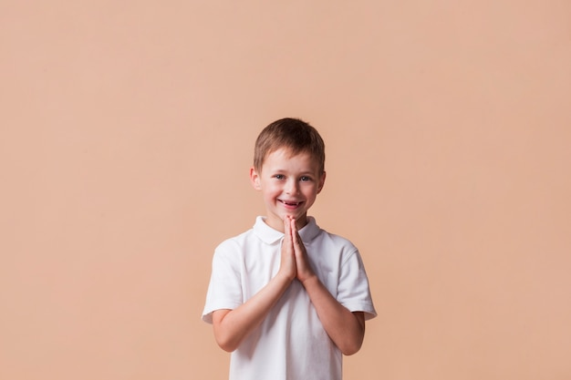 Portrait de garçon priant avec un sourire sur son visage sur fond beige