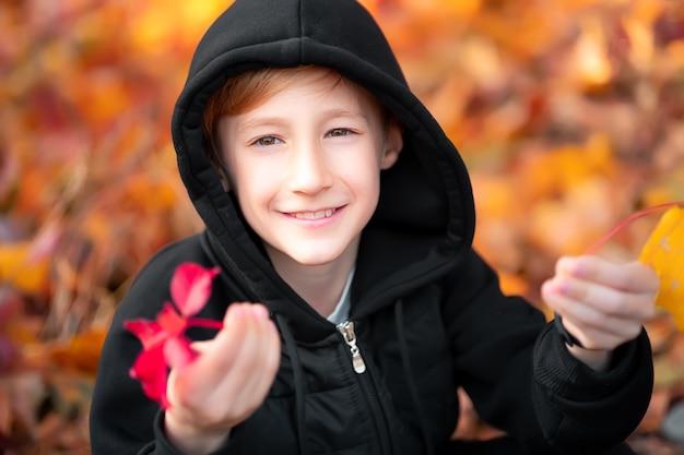 Portrait d'un garçon qui est dans le parc d'automne sur fond de feuilles.