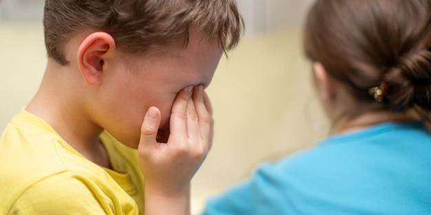 Portrait d'un garçon qui pleure sur un blanc