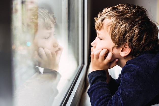 Portrait de garçon regardant par la fenêtre de sa maison s'ennuie