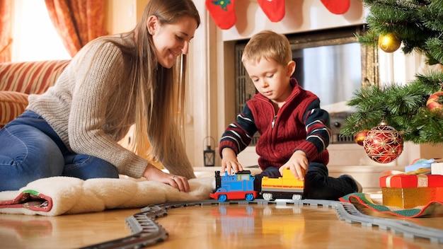 Portrait de garçon avec sa mère jouant sur le sol avec petit train et chemins de fer. enfant recevant des cadeaux et des jouets le nouvel an ou noël