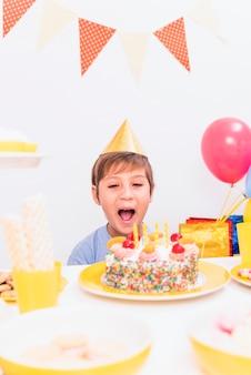 Portrait, garçon, souffler bougie, pendant, célébration anniversaire