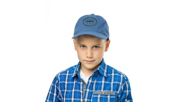 Portrait d'un garçon souriant dans une chemise et une casquette de baseball isolé sur fond blanc