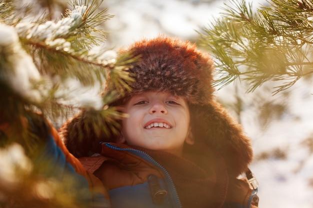 Portrait de garçon souriant dans une forêt enneigée en hiver