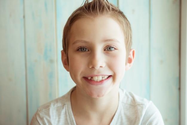 Portrait d'un garçon souriant. fond en bois clair