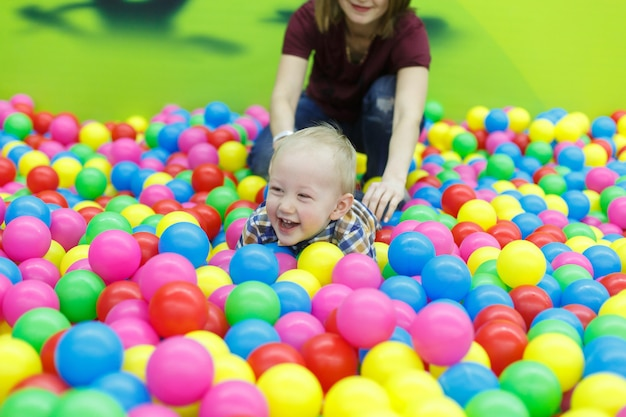 Portrait d'un garçon souriant joue au centre de jeu avec la mère. garçon drôle dans la piscine avec des boules multicolores. maman et fils s'amusent ensemble dans la salle de jeux se bouchent. enfance heureuse. week-end en famille.