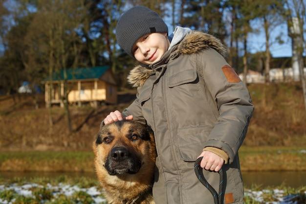 Portrait un garçon souriant marchant avec un grand chien de race berger allemand.