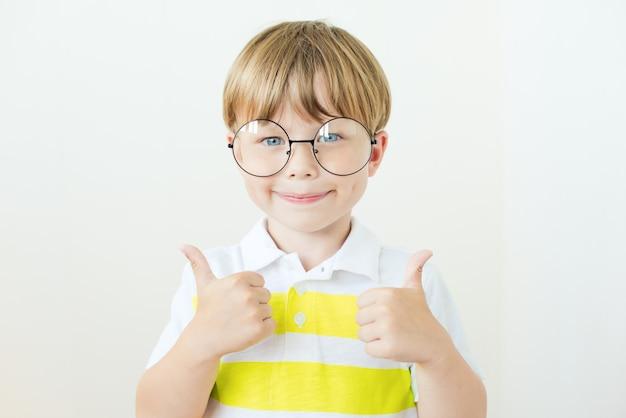 Le portrait d'un garçon souriant montre un coup de pouce sur un fond blanc