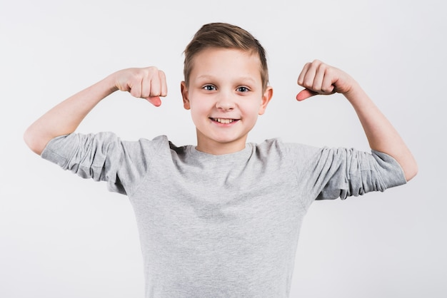 Portrait d'un garçon souriant, serrant son poing à la recherche d'appareil photo debout sur fond gris
