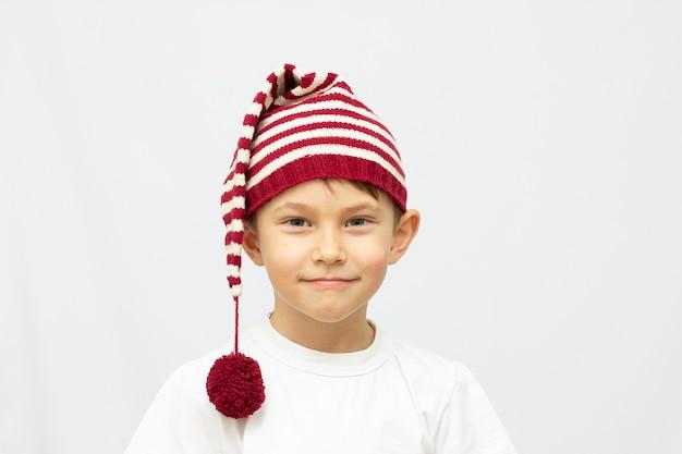 Portrait d'un garçon souriant de six ans dans un drôle de chapeau sur fond blanc
