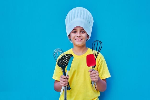 Un portrait de garçon souriant en t-shirt jaune et toque avec des ustensiles de cuisine prêt à apprendre à cuisiner