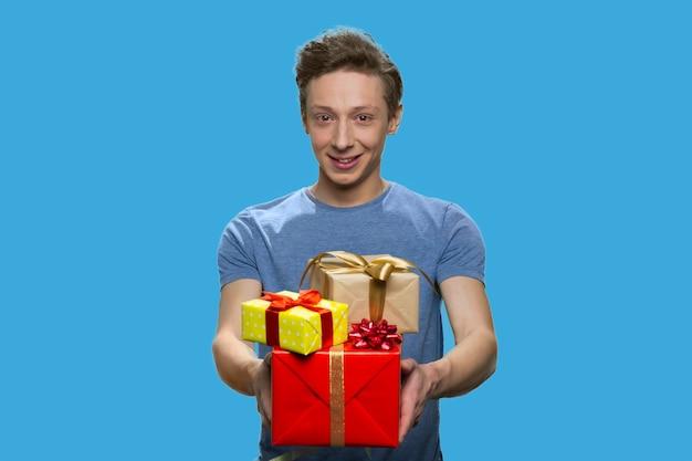 Portrait de garçon souriant en tshirt tenant des coffrets cadeaux