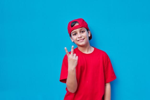 Un portrait de garçon en t-shirt rouge et casquette faisant le v pour la victoire avec sa main