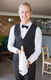 Portrait de garçon tenant une bouteille de champagne