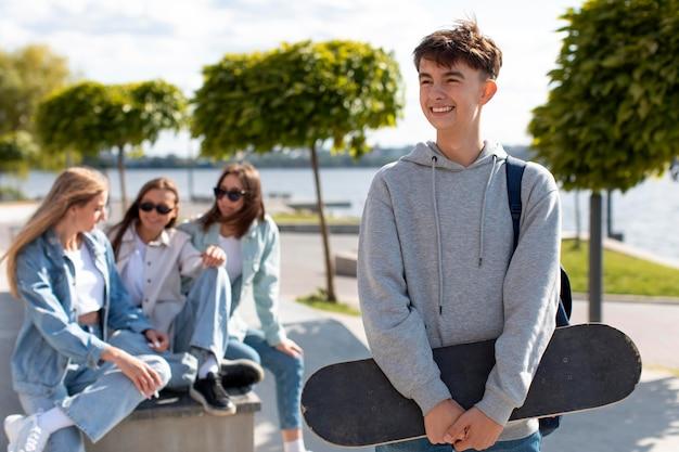 Portrait de garçon tenant une planche à roulettes à côté de ses amis