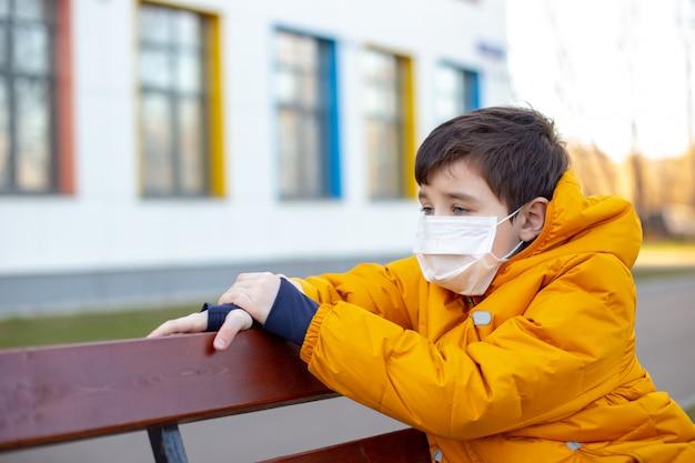 Portrait d'un garçon triste dans une veste jaune dans un masque médical blanc assis sur un banc dans la rue