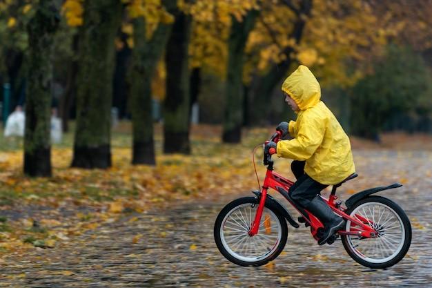 Portrait de garçon à vélo dans un parc d'automne sous la pluie. un garçon en imperméable jaune fait du vélo dans la ville.