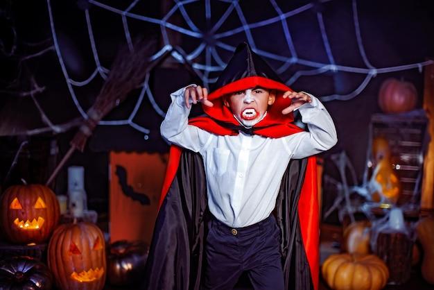 Portrait d'un garçon vêtu d'un costume de vampire sur fond grunge. fête d'halloween.