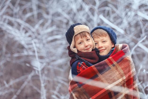 Portrait de garçons souriants dans une forêt enneigée en hiver