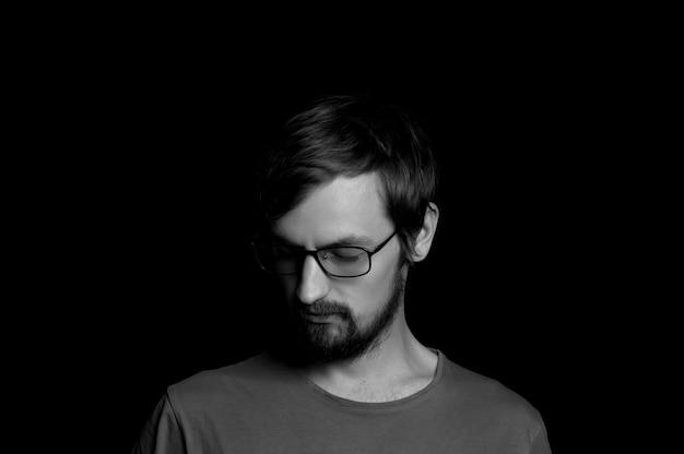 Portrait d'un gars avec une barbe à lunettes sur fond noir