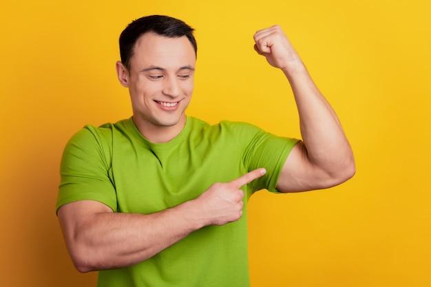 Portrait d'un gars brutal gai fort montre la main musculaire du doigt sur fond jaune
