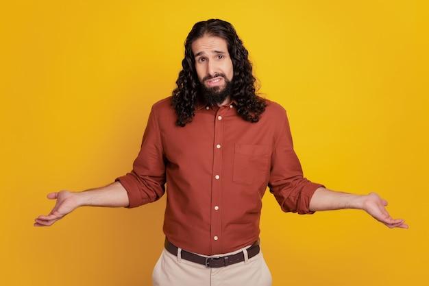 Portrait de gars désemparé a des doutes haussant les épaules sur fond jaune