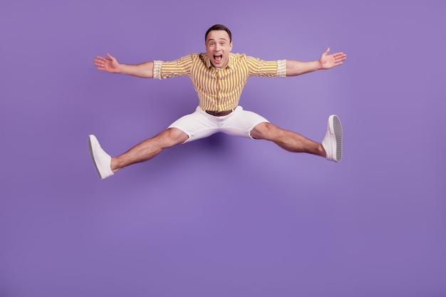 Portrait d'un gars énergique et sportif qui saute s'amuser le week-end sur fond violet