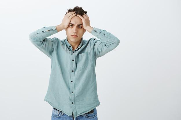 Portrait de gars européen fatigué en difficulté en chemise décontractée