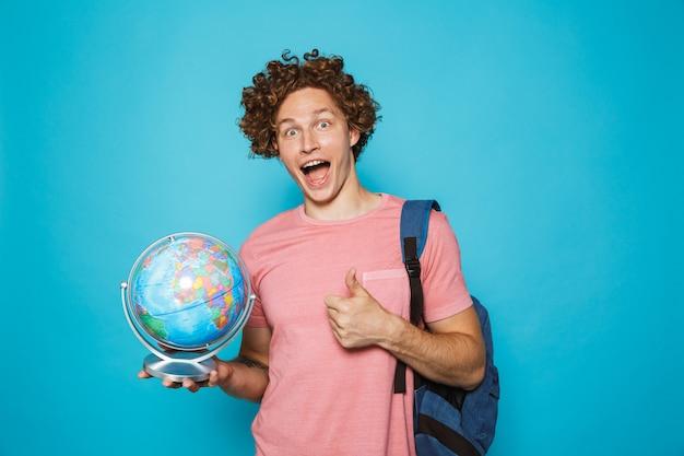 Portrait de gars excité européen avec des cheveux bouclés portant un sac à dos tenant un globe terrestre et montrant le pouce vers le haut