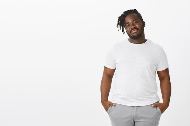 Portrait de gars facile à vivre avec des tresses posant contre le mur blanc