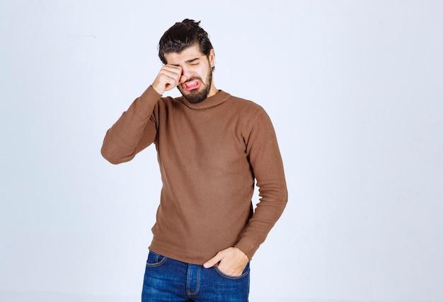 Portrait de gars fatigué avec des poils se frottant les yeux sur fond blanc gris. . photo de haute qualité