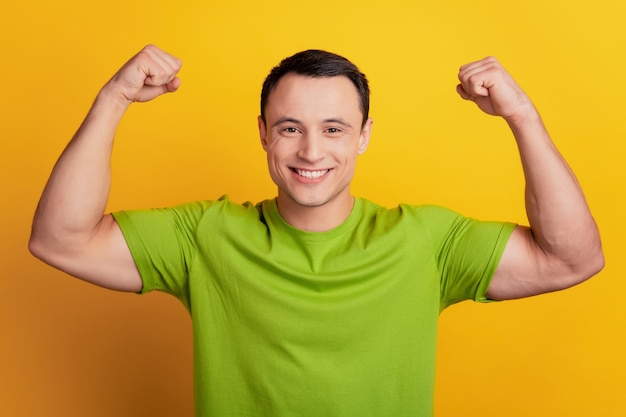Portrait d'un gars fort montre un grand concept de sport musculaire biceps sur fond jaune