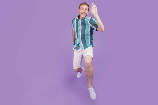 Portrait d'un gars gai positif et amical jump run vague main sur fond violet