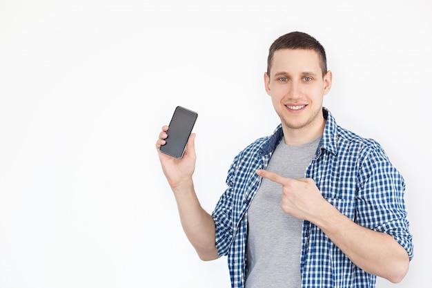 Portrait d'un gars gai, positif et attrayant avec du chaume dans une chemise, avec un smartphone avec un écran noir à la main, pointant son index sur un produit, isolé sur un blanc