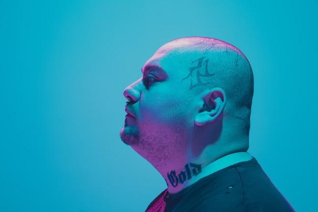 Portrait d'un gars hipster avec néon coloré sur mur bleu. modèle masculin d'humeur calme et sérieuse.